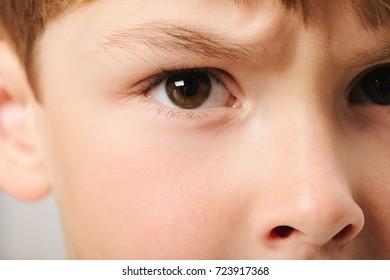 Caucasian European school boy with blond hair and brown eyes, closeup portrait