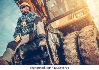 Caucasian Excavator Operator Sitting on His Excavator. Heavy Duty Ground Working Machinery. Construction Industry.