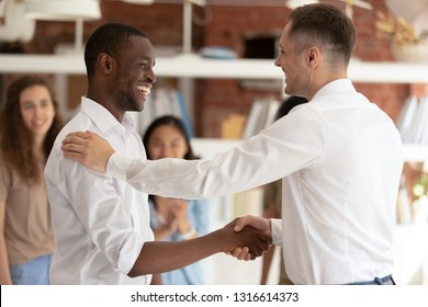 Caucasian executive boss handshaking promoting successful happy african black worker expressing gratitude praising shaking hand appreciating for good work, reward recognition acknowledgement concept