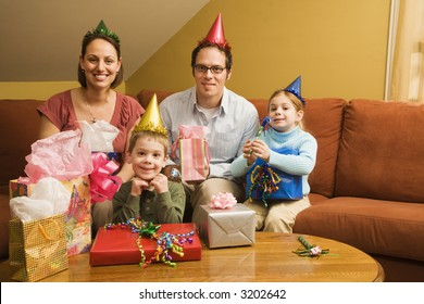 Caucasian family celebrating a birthday party and looking at viewer.