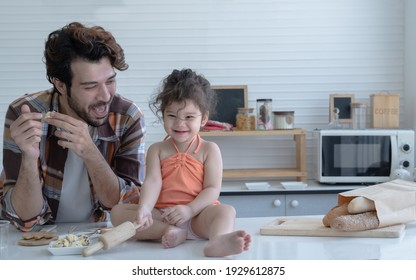 Caucasian family father and little daughter cooking in the kitchen at home. Cute girl holding rolling pin in her hand while dad smile and looking at his lovely child with love at home