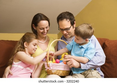 Caucasian family on couch looking at Easter basket.