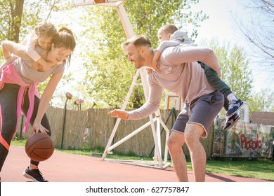 Caucasian family playing basketball together. Parents carrying their children on piggyback.