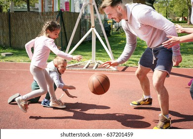 Caucasian family playing basketball together. Single father spending time with his children.