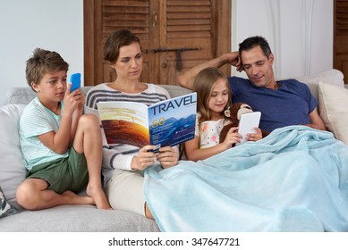 Caucasian family relaxing at home mom reading magazine kids playing games on tablet device and mobile cell phone