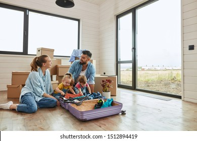 Caucasian family sit on floor, man and woman look each other unpack suitcase in new house. Behind them moving boxes, door, window. Man keep on knees girl who interested in unpacking.