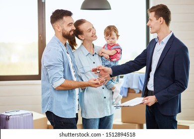 Caucasian family of three people take keys new big house from realtor. They smile. Background moving boxes, big window.