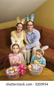 Caucasian family wearing rabbit ears with Easter baskets looking at viewer.