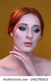 caucasian fashion model with bright green make up, dyed red hair, straight nose, full lips and big eyes, posing on a yellow background, headshot, beauty photography