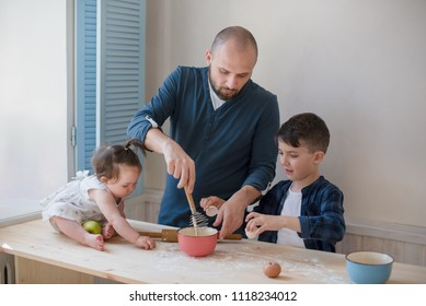Caucasian father and children baking together in the kitchen.