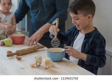 Caucasian father and children baking together in the kitchen with a little chicks on table.