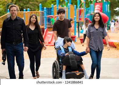 Caucasian father and four biracial teen children walking past playground with disabled boy in wheelchair. Son has cerebral palsy
