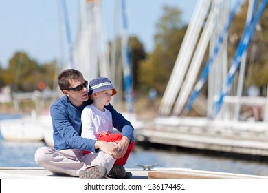caucasian father and his son sitting at a marina dock together