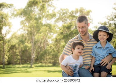 Caucasian father outdoors with his 2 mixed race Asian Caucasian sons on the older brother's first day of school