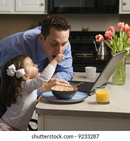 Caucasian father in suit using laptop computer with daughter feeding him breakfast in kitchen.