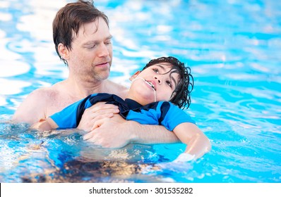 Caucasian father swimming in pool with biracial disabled son in his arms. Child has cerebral palsy.
