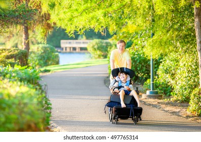 Caucasian father taking walk with ten year old biracial disabled son in wheelchair at park on sunny day