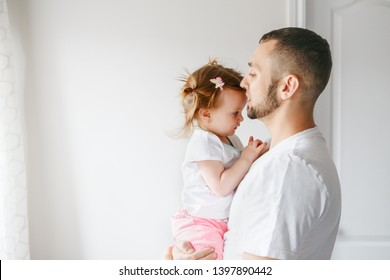 Caucasian father talking speaking with toddler baby girl. Male man parent holding embracing child daughter. Authentic lifestyle touching tender moment. Single dad family life concept. Happy fatherhood