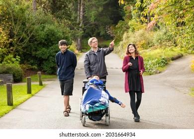 Un père caucasien marchant avec des enfants métis dans un parc, poussant son fils handicapé en fauteuil roulant. Famille multilingue.