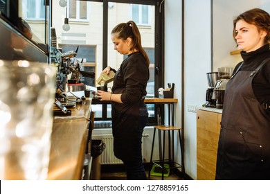 Caucasian female barista in black uniform pouring milk for cappuccino. Skilled waitress in apron standing near her. Coordinated work together concept