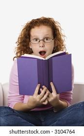 Caucasian female child sitting reading book looking surprised.