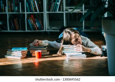Caucasian female college student lying on floor in library with red cup and many books around , reading book. Side view, full length, copy space. The concept of education and learning.