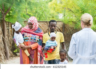 Caucasian female doctor visiting one African black family in village