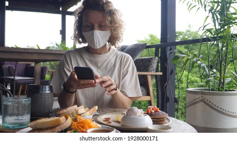 Caucasian female food blogger taking pictures of her vegan lunch in an outdoors restaurant