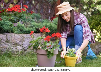 Caucasian female gardener in working clothes and with gardening gloves planting begonia while crouching. Backyard exterior.
