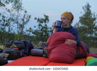 caucasian female hiker drinking beverage from cup while wild camping outdoors