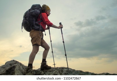 caucasian female hiker hiking on a rocky alpine trail
