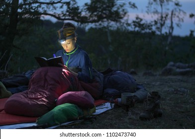 caucasian female hiker reading book/writing journal at night while wildcamping, strong light from headlamp