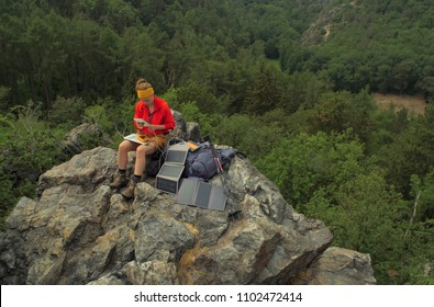 caucasian female hiker sitting on a rock while working on a laptop being charged by solar panels nearby,  portable solar charing technology concept