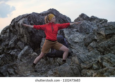 caucasian female hiker stretching her body on a alpine trail next to her backpack, getting ready to go