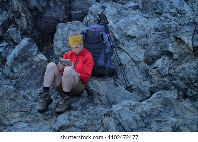 caucasian female hiker using portable tablet technology outdoors on a alpine hiking trail