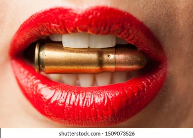 Caucasian female lips wearing red lipstick biting a bullet, aggression concept