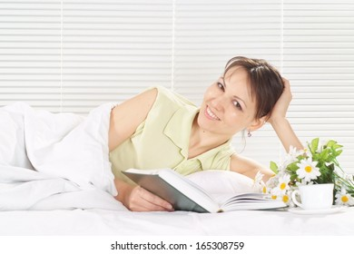 Caucasian female lying in a bed of book on a light