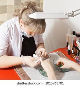 Caucasian female manicurist removing cuticles with nipper