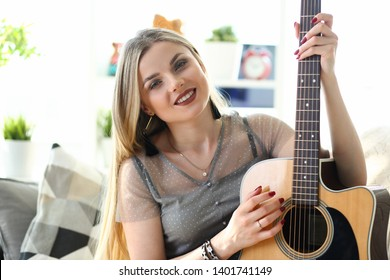 Caucasian Female Musician Playing Music at Home. Attractive Woman Holding Guitar. Young Blonde Sitting on Sofa Head and Shoulders Front Shot. Beautiful Milennial Girl Leisure Perfomance