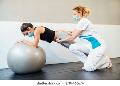 Caucasian female physical therapy professional at a clinic giving a pilates lift treatment with a therapy ball to a client with a face mask due to the covid 19 coronavirus pandemic.