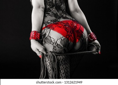 Caucasian Female in Sexy Lingerie Posing with Rope for BDSM Role Game.In red Handcuffs and Net Pantyhose. Toned and Desaturated  Image. Horizontal Orientation