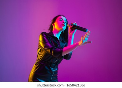 Caucasian female singer portrait isolated on purple studio background in neon light. Beautiful female model in black wear with microphone. Concept of human emotions, facial expression, ad, music, art.