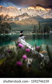 Mujer caucásica sentada en una piedra cerca del lago Eibsee, Alemania. Concepto de viajes, estilo de vida.