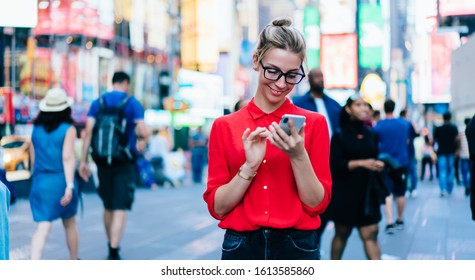 Caucasian female standing in crowded square with mobile phone in hands.Addicted to social network. Millennial technology user. Young woman browsing internet via app on smartphone. Tourist explore city