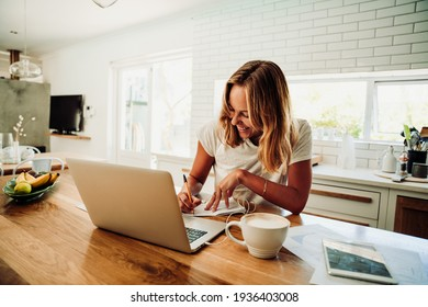 Caucasian female student working from home writing in note pad with laptop sitting next to hot coffee