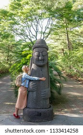 Caucasian Female Tourist Hugging Dol hareubang, also called tol harubang, hareubang, or harubang - Traditional Statue Guard of Jeju Island in South Korea. Sculpture Made of Volcanic Rock