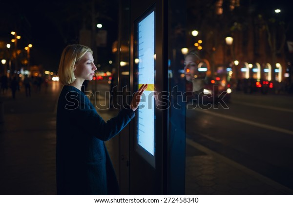 Weibliche Weibchen, die eine automatische Bankmaschine mit großem digitalen Bildschirm verwenden, während sie in Nachtlichter außerhalb der Stadt stehen, überprüfen über ein modernes Gerätesymbol den Kontostand bei der Bankanwendung