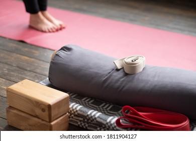 Caucasian females legs on yoga mat. Yoga props for Iyengar lesson.