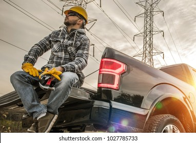 Caucasian Field Worker with Tools. Caucasian Men Wearing Safety Gloves and Hard Hat Seating on the Back of His Pickup Truck. Contractor in the Field