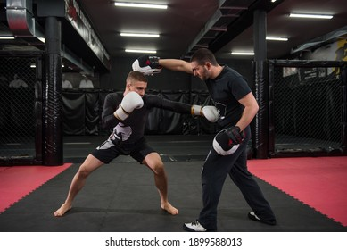 Caucasian fighter at kickboxing training practicing punching, kicking and sparring with his trainer.